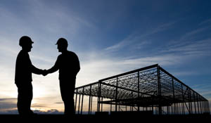 Two men shaking hands in front of a construction site